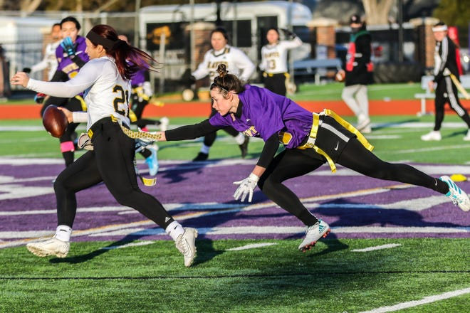 Kansas Wesleyan's Carlee Becker (3) lays out in an attempt to grab the flag off Ottawa's Madysen Carrera during Sunday's game at Graves Family Sports Complex.