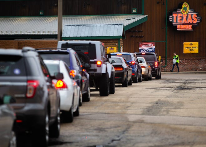 """Cars line up for the drive-thru during the dinner service at Texas Roadhouse, Friday, March 27, 2020, in Springfield, Ill. """"We are grateful and shocked by the amount of to-go business we have had,"""" said Amanda Eilers, with the Springfield Texas Roadhouse. """"Everyday we've had to add more parking spots."""" [Justin L. Fowler/The State Journal-Register]"""