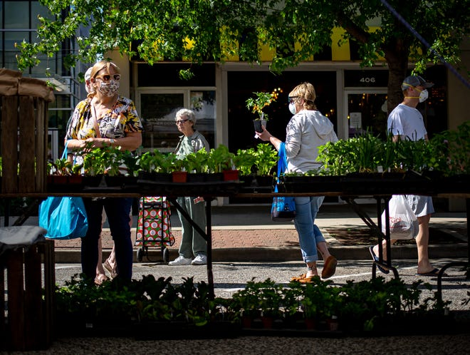 Customers shop the Harvest & Blooms Farm booth at the Old Capitol Farmers Market on Adams Street, Saturday, May 16, 2020, in Springfield, Ill.