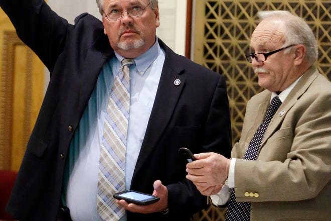 """FILE - In this Monday, April 6, 2015 file photo, Rep. Bud Hulsey, R-Kingsport, right, attends a House session in Nashville, Tenn. At left is Rep. Mike Harrison, R-Rogersville. In 2021, Hulsey is pushing legislation that would ban most government agencies from requiring COVID-19 vaccines, trying to drum up support for his bill by downplaying the seriousness of the disease. Hulsey faced pushback from a fellow Republican, Rep. Sabi Kumar, a surgeon who has been a rare GOP advocate for proper mask-wearing while lawmakers gather at the Tennessee Capitol. """"The concern I have is that (the bill) creates an anti-vaccine attitude,"""" Kumar said.(AP Photo/Mark Humphrey)"""