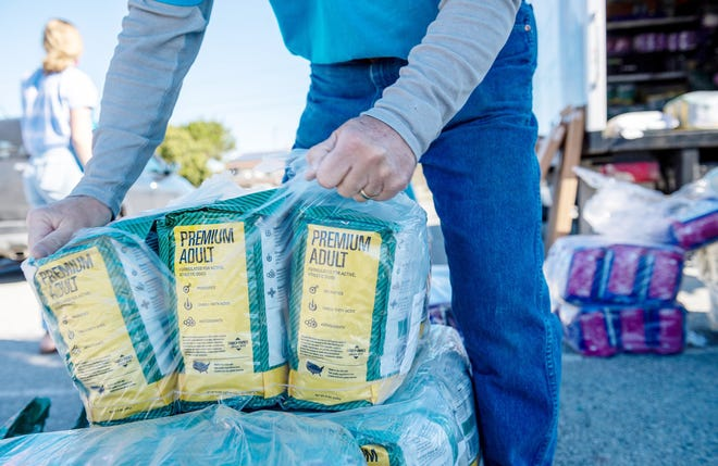 A free pet food program may be a new development in Southeast Kansas but such programs are not unheard of. A volunteer, shown here, opens a case of dog food during an SPCA giveaway last month in California.