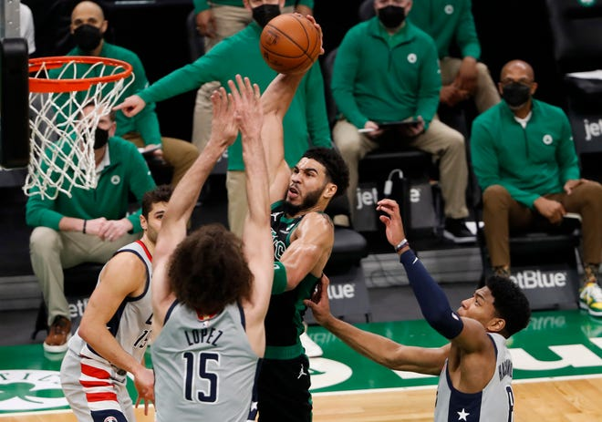 Celtics forward Jayson Tatum drives in for a dunk over Wizards center Robin Lopez (15) during Sunday night's victory at TD Garden.