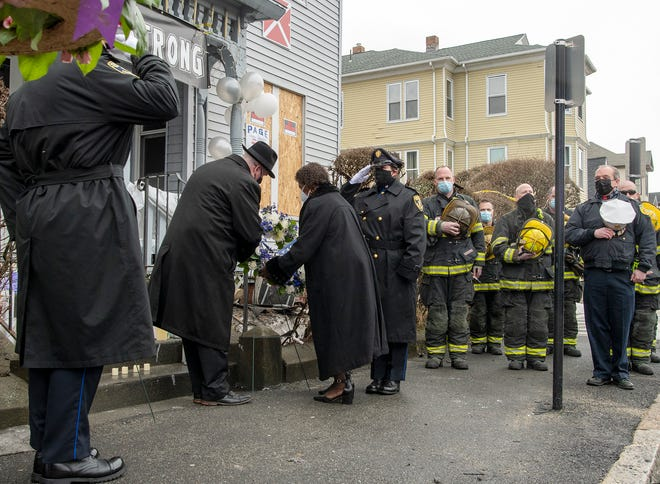 Lorraine S. Adams places a wreath in memory of her brother, Gerald F. Prince, in front of 13 Jaques Ave., as officers from the Massachusetts Trial Court and Worcester Firefighters pay their respects.