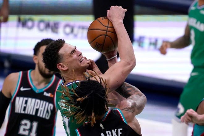 Dallas Mavericks' Dwight Powell, top center, is fouled taking a shot by Memphis Grizzlies' Brandon Clarke, bottom center, in the second half of an NBA basketball game in Dallas on Feb. 22. [AP Photo By Tony Gutierrez]