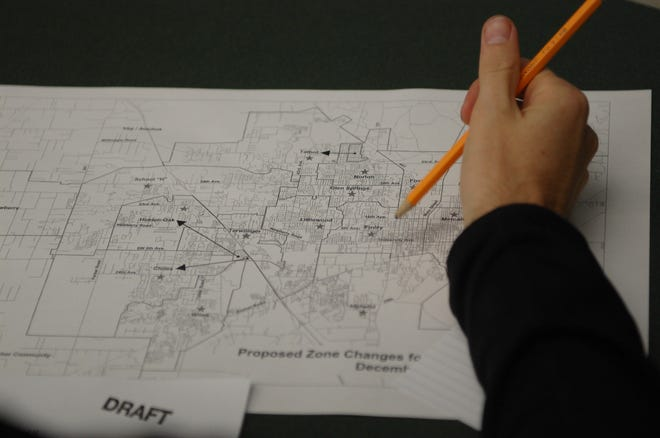 An attendee at a public input session looks over a school zoning map at Westwood Middle School in 2011.