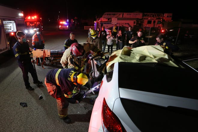 Firefighters pry door open to free woman injured in traffic accident on Highway 119 and East Kern Saturday evening.