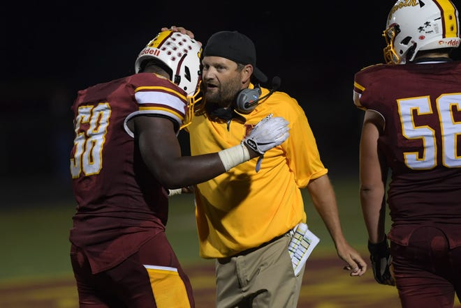 Westerville North coach Bryan Johnson talks with Reuben Simiyu (58) during a game last season. Simiyu has been selected as an Ohio North-South all-star by the Ohio High School Football Coaches Association, while Johnson was selected as an assistant coach for the South all-stars.