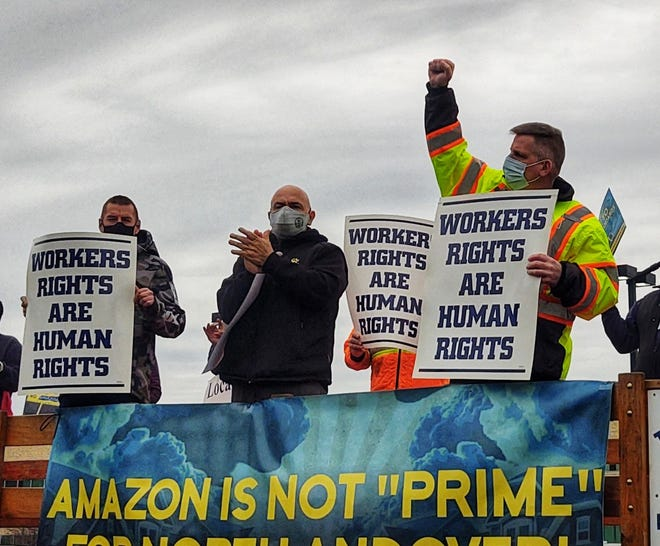 Labor union members and representatives protested outside the the site of the planned Amazon distribution center in North Andover Monday, demanding the company hire union workers and offer higher wages and better worker protections.