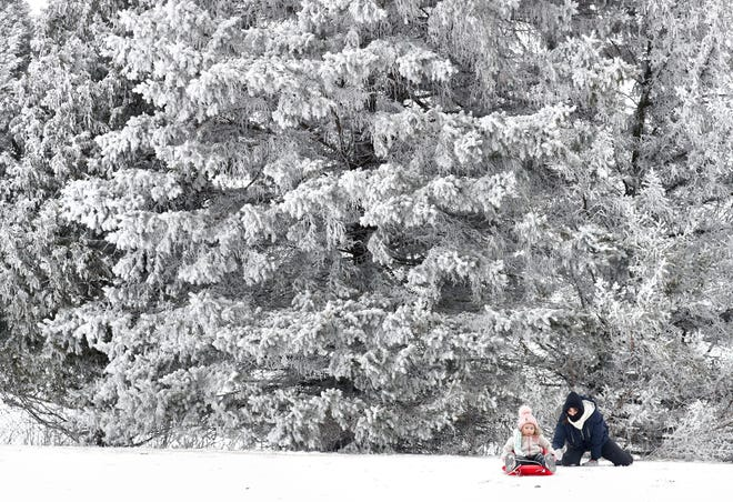 Magnolia, Lucht, 2, gets a little push from her mother Shana Lucht while sledding Monday, January 4, 2021, at Plamann Park in Appleton, Wis.