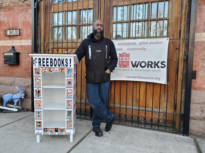 Photographer Erik James Montgomery shows a book ark he adorned with his work outside Camden FireWorks, the gallery where he has a studio.