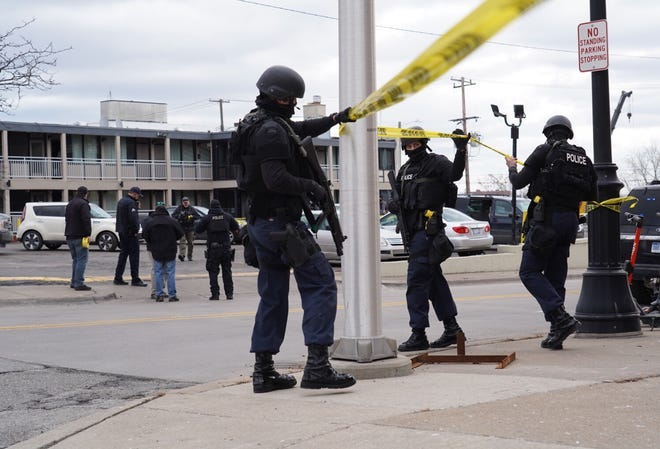 Detroit police officers adjust caution tape on scene at Rivertown Inn & Suites in Detroit on Monday, March 1, 2021 where police shot a man from Cincinnati suspected of shooting five people, killing three.