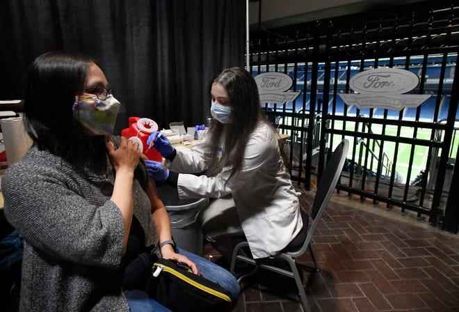 Bernice Rutherford dari Utica Schools mendapatkan vaksin COVID-19 dari apoteker Meijer Maya Abdullah. Meijer menyelenggarakan klinik vaksin COVID-19 di Ford Field khusus untuk pendidik dan staf pendidikan di Detroit pada 1 Maret 2021.