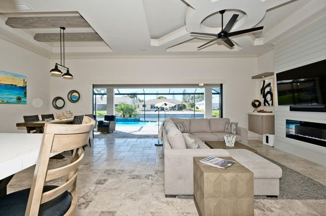 The living room features a ceiling with a white beam circle inlay. This model by SPO Construction just sold right before the 35th Annual Lee County Building Industry Association Parade of Homes.