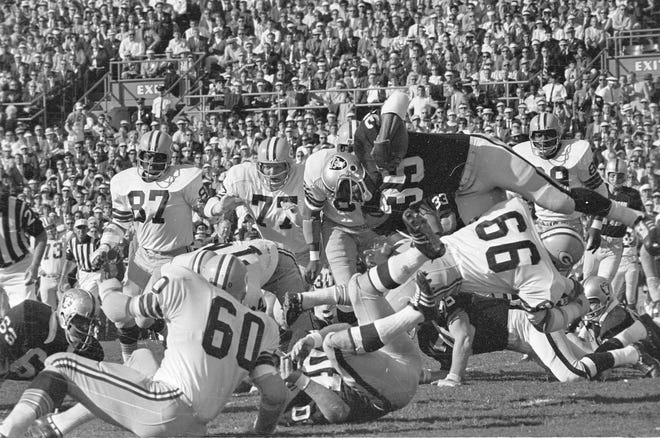 Green Bay Packers linebacker Ray Nitschke (66) cuts through the block of Oakland Raiders tackle Bob Svihus (76) to stop fullback Hewritt Dixon (35) during Green Bay's 33-14 victory over Oakland in Super Bowl II at the Orange Bowl in Miami on Jan. 14, 1968. Packers linebacker Lee Roy Caffey (60) and Raiders fullback Pete Banaszak (40) are on the ground, with Packers defensive linemen Willie Davis (87) and Ron Kostelnik (77) watching the play from behind.