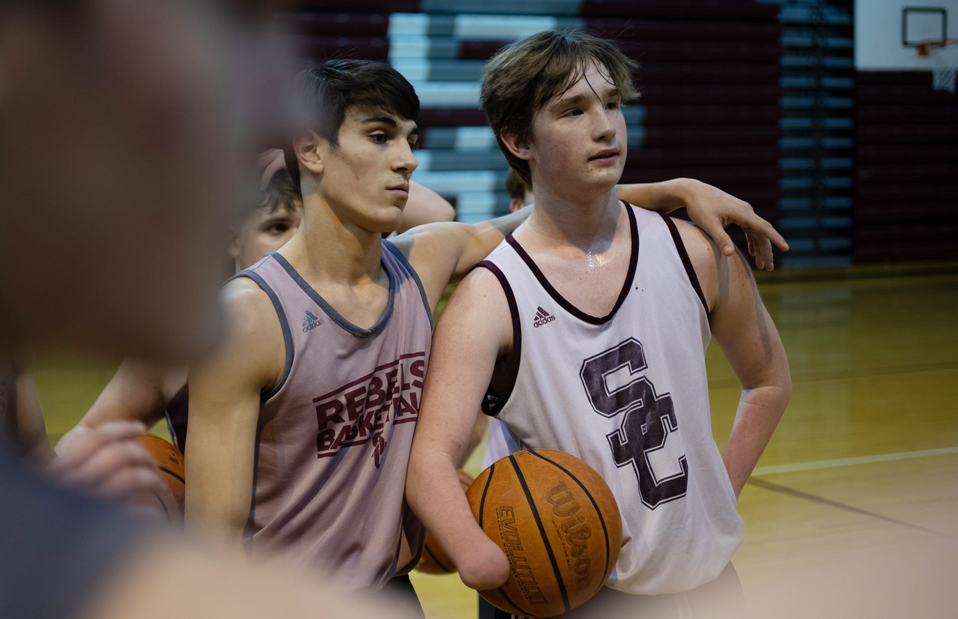 """Kole Stewart (left) puts his arm around Landis Sims on Wednesday, Feb. 24, 2021, as head coach Greg Robinson  gives instructions during practice. """"You know, you worry 'Can he do this or not?,'"""" Robinson said. """"But, that went out the window, probably, day or two of practice this year."""" Sims' first shot of the year was a trailing three point swish."""