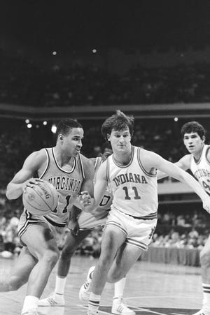 Virginia's Othell Wilson (left), moves the ball past Indiana's Dan Dakich during early action of the NCAA East Regional in 1984. (AP Photo)