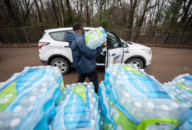 Derrick Kelly gives a Jackson resident a case of water at Forest Hill High School in Jackson, Miss., Monday, March 1, 2021. Water is still being distributed due to water outages around the city after February's winter storm.