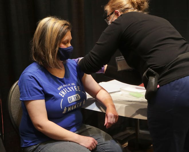 Christie Kessler, a day care teacher at Grandma's House Child Care Center in Wauwatosa, gets a COVID-19 vaccine shot from registered nurse Nicki Pantuso at the Wisconsin Center in Milwaukee on Monday, the first day teachers became eligible for the vaccine.
