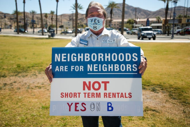 Palm Desert resident Bruce Poynter holds a sign in support of Measure B on Monday, March 1, 2021, in Cathedral City, Calif. A special election for the city on March 2 will decide whether most short-term vacation rentals should be phased out in the city by 2023. Poynter said short-term rentals are a valley-wide issue.