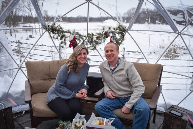 Abbey and Jerod Smith of Norwalk enjoy dinner, as well as snowy views of the 60-acre estate, inside an igloo at Twin Oast Brewing on February 17.