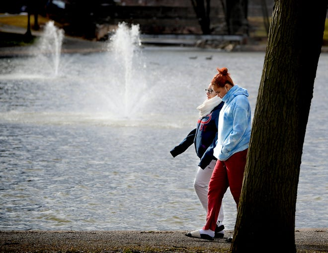 Sisters Maria, left, and Luisa Tejada, both of Harrisburg, walk along Kiwanis Lake in York City Monday, March 1, 2021. They were visiting friends in York. A project to beautify the lake and improve water quality is expected to be completed by June. Bill Kalina photo