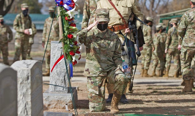 A member of the U.S. military salutes the plaque for 1st Lt. Mark Mathis at Fairmount Cemetery during a ceremony Sunday, Feb. 28, 2021.