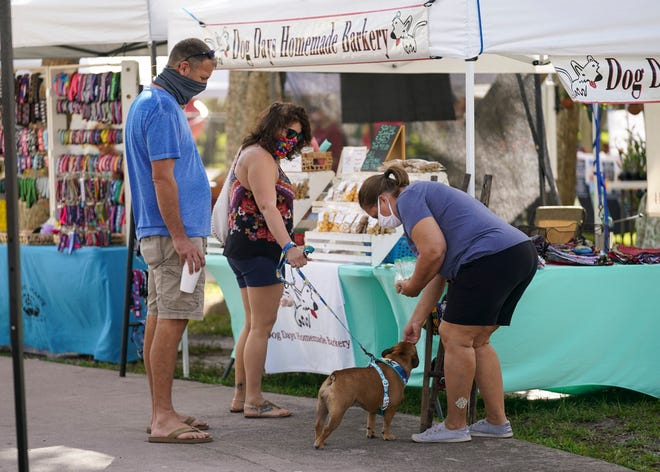 """Vendor Amy Byrd (right), of Dog Days Homemade Barkery, gives one of her homemade treats to a French bulldog named Cora Cay while accompanied by her owners, Jason Litterick (left) and Kyra Lewis, during the Stuart Green Market at Flagler Park on Sunday, Feb. 28, 2021, in downtown Stuart. """"I like that we're down here, I know traffic isn't coming down here yet but I do like the atmosphere,"""" said Byrd. """"Since we're pet friendly the dogs can come walk. It's nice and cool."""" The market is held every Sunday from 9 a.m. until 2 p.m., rain or shine."""