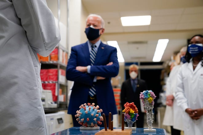FILE - In this Thursday, Feb. 11, 2021 file photo, President Joe Biden visits the Viral Pathogenesis Laboratory at the National Institutes of Health (NIH) in Bethesda, Md. At bottom center is a model of the COVID-19 virus.