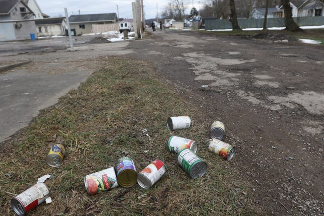 A pile of cans sits in the grass beside an ally in the Putnam neighborhood of Zanesville.