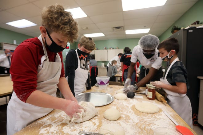 Cord Shriner, left, kneeds pizza dough while Clayton Cannon watches during a cooking class for elementary school students at New Lexington High School recently. At right, Chef Aldwayne Segree helps Emersyn Adams with his dough.