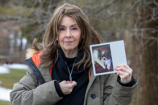 Rhonda Bomwell, of Somerset, N.J., holds a necklace with her dog's ashes and a photograph of her 9-year-old Papillon, Pierre, that died June 1, 2020, because of side effects from wearing a popular flea and tick collar for pets. Bomwell, seen Monday, March 1, 2021, had never used a collar on Pierre because he was mostly an indoor animal.