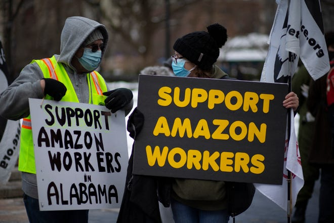 In this file photo, people hold placards during a protest in support of Amazon workers in Union Square, New York on February 20, 2021. - US President Joe Biden on February 28, 2021 supported Amazon workers' right to form unions, but it did not go as far as explicitly encouraging them to form Syndicate.