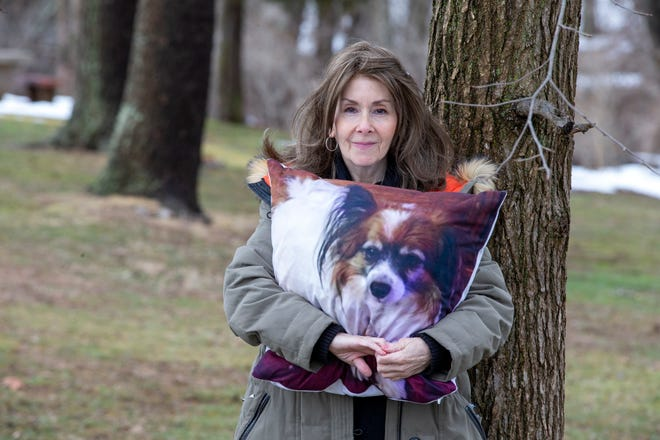 Rhonda Bomwell, of Somerset, N.J., holds a pillow Monday, March 1, 2021, with the image of Pierre, her 9-year-old Papillon, that died June 1, 2020, from side effects of wearing a popular flea and tick collar for pets.