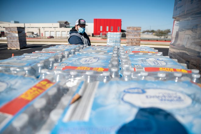 Cody Wofford unloads bottled water from a truck on Feb. 20 at Del Valle High School to help people who lost water after the winter storm. Requests for legal aid have increased significantly over the past year, as Texans grappled with problems from the pandemic and now, the winter storm. (Sergio Flores for AMERICAN STATESMAN)