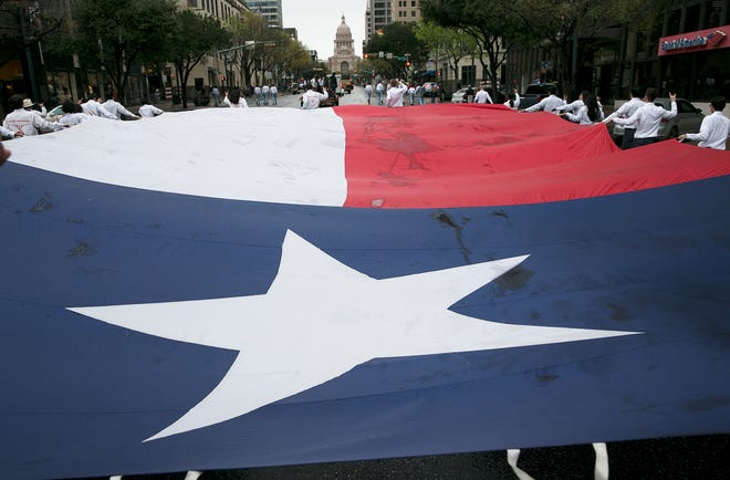 The Texas flag moves up Congress Avenue toward the Capitol carried by UT's Alpha Phi Omega during the Texas Independence Day Parade on March 4, 2017.
