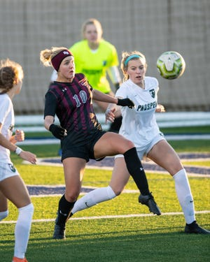 Round Rock's Jordan Doss, left, battles for controls of the ball in a tournament match against Prosper earlier this season. Doss had two goals in a 2-2 draw with Vandegrift last week, including a second-half equalizer that kept the Dragons unbeaten in District 25-6A.