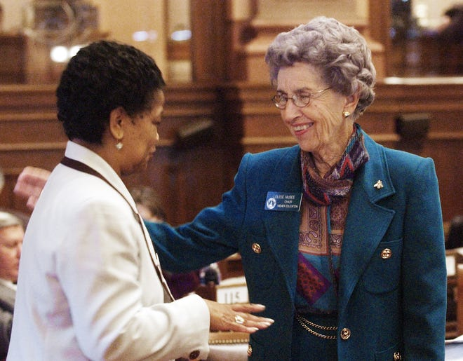 Rep. Louise McBee, D-Athens, right, chairman of the Higher Education Committee, talks with legislative aide Alexis Gary Redding on the floor of the House in Atlanta on Thursday, Feb. 19, 2004. McBee led efforts to cut costs from the HOPE scholarship. (AP Photo/Ric Feld)