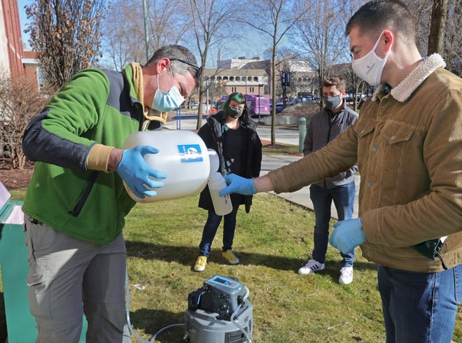 John Senko, a University of Akron associate professor of geosciences and biology, works Tuesday with senior student Blake Bilinovich, right, to gather wastewater from Williams Honors College to test for signs of COVID-19.