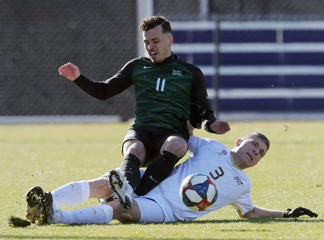 The University of Akron's Carlo Ritaccio, bottom, collides with Marshall's Jamil Roberts during the first half of the Zips' 2-1 overtime win Tuesday in Akron. [Jeff Lange/Beacon Journal]