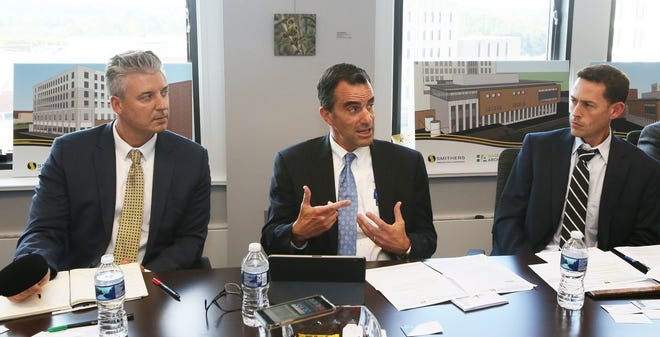 Smithers executives Glenn Goldney, left, vice president of sales and marketing, and CFO Michael Hollabaugh listen to Nathaniel Leonard of materials science and engineering discuss plans to move Smithers headquarters to downtown Akron during a Sept. 16, 2019, news conference.