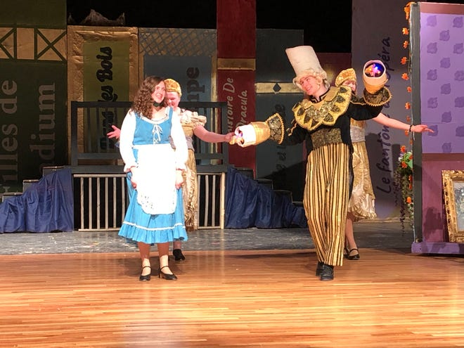 """Boone High School """"Beauty and the Beast"""" production cast members performing the """"Be Our Guest"""" scene with Carlee Carpenter as Belle and Ben Lumley as Lumiere."""