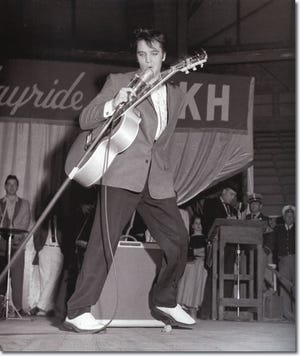 Elvis performing on the Louisiana Hayride stage at the Shreveport Municipal Auditorium.