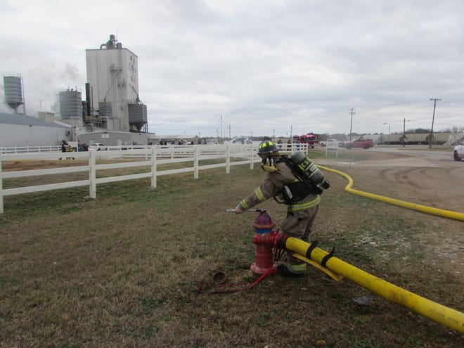 Brownwood firefighter Eric Hunter turns on the water flow at a hydrant near the Ethos pet food plant on Stephen F. Austin in Brownwood around noon Monday. Firefighters from Brownwood and Early responded to a dryer fire inside the plant that caused no injuries.