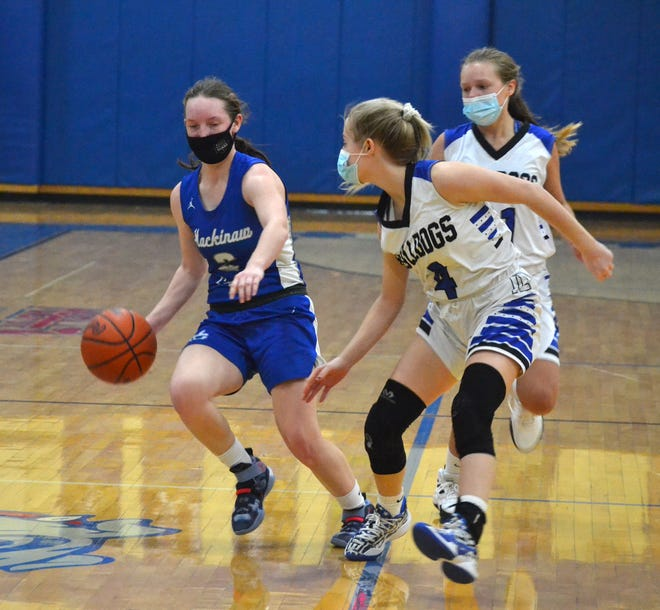 Mackinaw City junior guard Gabi Bell (left) looks to get past Inland Lakes senior guard Christy Shank during the second half of a varsity girls basketball contest in Indian River on Monday.