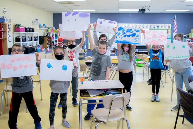 """Third-grader students at Cambridge Intermediate fingerpainted Truffula trees for the Dr. Seuss classic """"The Lorax.""""  """"Wocket in My Pocket"""" bookmarks and """"The Cat in the Hat"""" fruit skewers were also part of the day's activities.  –"""