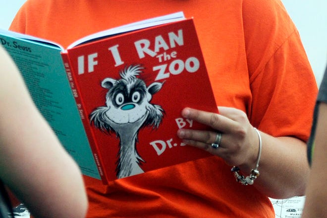 """In this Sept. 24, 2013, file photo, Courtney Keating, education coordinator of The Literacy Center in Evansville, Ind., reads """"If I Ran the Zoo,"""" by Dr. Seuss, to passersby during an event to promote literacy along the Evansville Riverfront. Dr. Seuss Enterprises, the business that preserves and protects the author and illustrator's legacy, announced on his birthday, Tuesday, March 2, that it would cease publication of several children's titles including """"And to Think That I Saw It on Mulberry Street"""" and """"If I Ran the Zoo,"""" because of insensitive and racist imagery."""