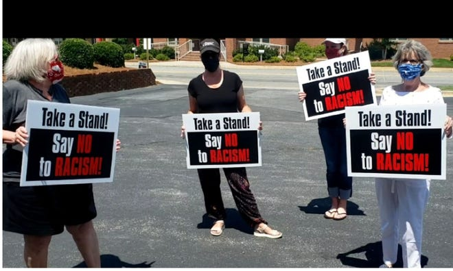 """Members of PFLAG Lexington/Davidson County used the funds raised from the sale of """"Say No to Racism"""" yard signs to provide scholarships for local students."""