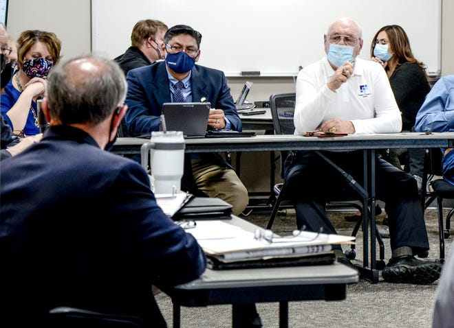 Finney County Commissioner Dave Jones, right, asks a question during a discussion on housing Monday at a joint meeting between the county commission, the Garden City commission and Holcomb's commission. Garden City commissioners Deb Oyler and Manny Ortiz are shown at left.