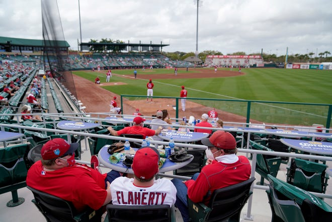 Fans sit in socially distant pods as they watch a spring training baseball game between the Washington Nationals and St. Louis Cardinals on Sunday, Feb. 28, 2021, in Jupiter, Fla.