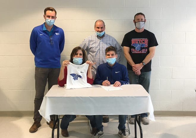Central Christian High School senior Collin Oswalt has signed to run track and cross country at Hutchinson Community College Monday and is welcomed by HCC's head cross country coach Justin Riggs, left, and HCC's head track coach Robert Spies, right, with Collin's parents Dick and Megan Oswalt.